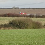 Arable crops being sprayed, as viewed from the gap in the hedge