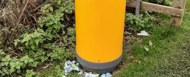 The waste bin opposite the shop